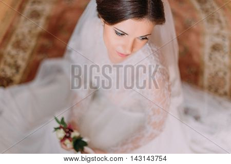 Close-up portrait of beautiful innocent bride in wedding dress sitting on carpet and holding cute floral boutonniere.