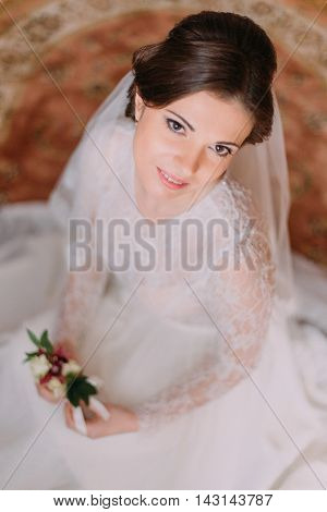 Close-up portrait of beautiful smiling bride in wedding dress sitting on carpet and holding cute floral boutonniere.