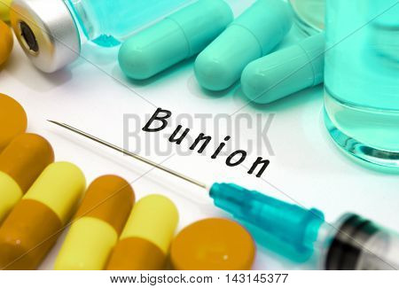 Bunion - diagnosis written on a white piece of paper. Syringe and vaccine with drugs.
