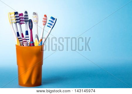 Various colorful toothbrushes in yellow cup on bright blue background with color gradient. The image has copy-space on the right side.