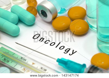 Oncology - diagnosis written on a white piece of paper. Syringe and vaccine with drugs