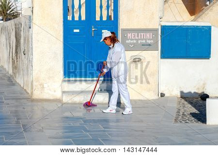 Oia, Greece - April 27, 2016: A cleaning lady washes the street in the village Oia in the early morning on the island Santarini. Village daily visited by many tourists.