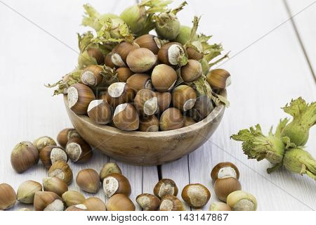 Bowl of fresh hazelnuts on the wooden background