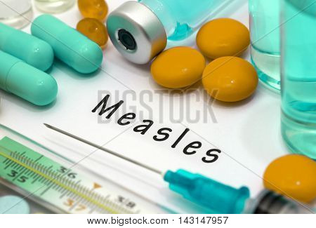 Measles - diagnosis written on a white piece of paper. Syringe and vaccine with drugs.