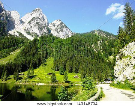 View Idyllic, beauty alpine landscape in Austria: lake, mountains, green grass, blue sky. Beautiful view on the Lake Gosau and Austrian Alps, Salzkammergut region, Upper Austria, Austria, Europe