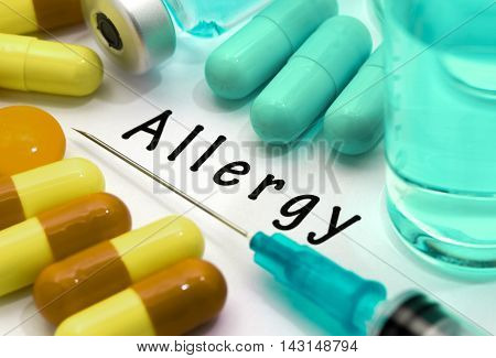 Allergy - diagnosis written on a white piece of paper. Syringe and vaccine with drugs.