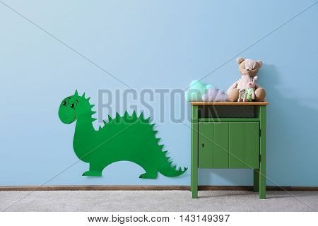 Green bedside table with toys and dinosaur on blue wall background