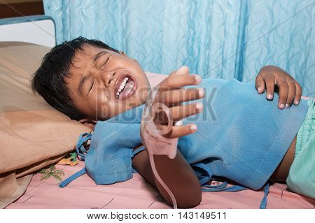 Little boy sick and crying on patient bed