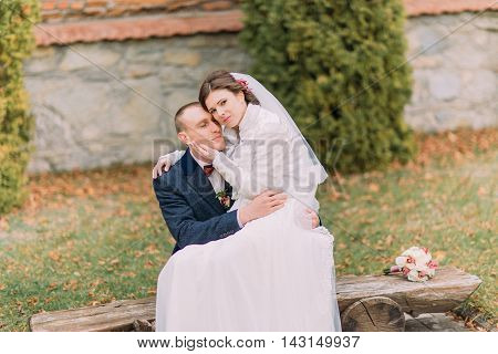 Happy just married couple in autumn park. Elegant bride sitting on knees of her handsome new husband.