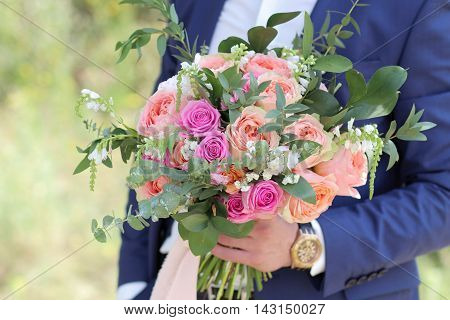 Beautiful Bridal Bouquet In Hands Of The Groom. Wedding Bouquet Of Peach Roses By David Austin,  Sin