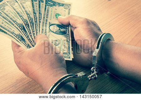 Hand young man in handcuffed hold money vintage tone