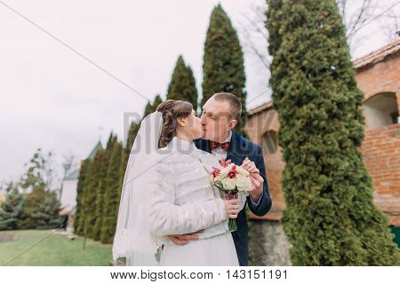 Handsome groom tenderly kissing his elegant new wife near cypress trees and fortified wall in romantic park.