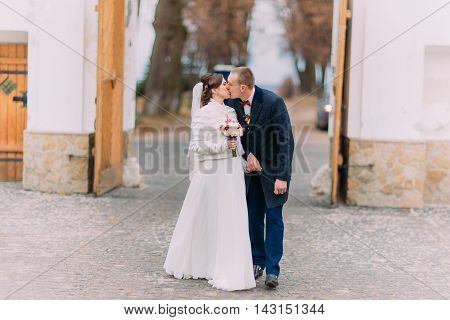 Beautiful young newlywed pair kissing in front ofthe gateway.