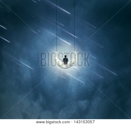 Surreal background with a boy sitting on a crescent moon as a swing over a misty night sky