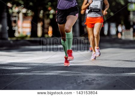 feet young woman athletes compression socks running marathon