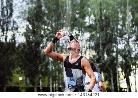 Ekaterinburg Russia - August 7 2016: male athlete runner hot weather pouring water on head during Marathon Europe-Asia
