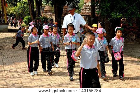 Autthaya Thailand - December 20 2010: A group of Thai schoolchildren in their pink and blue uniforms pay a visit to historic Wat Phra Si Sanphet