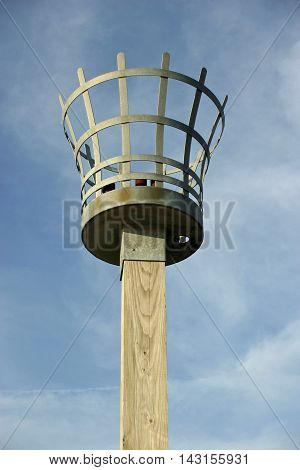 Beacon to be used with either a fire gas or electric light. Metal basket construction. On a wooden post. Background of blue sky with white cloud.