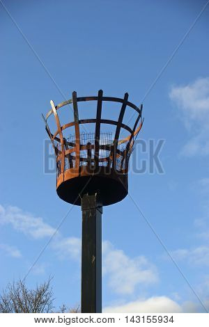 Beacon to be used with a fire. Outer metal basket construction with an inner basket for the fire. Metalwork rusted. On a wooden post. Background of blue sky with white cloud and tree without leaves in the lower left corner.