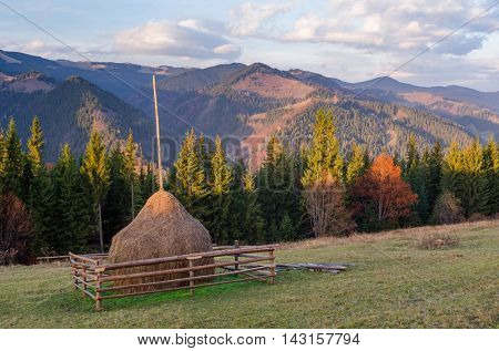 Autumn landscape at sunset. Haystack on the meadow in a mountain village. Sky with beautiful clouds. Carpathians, Ukraine, Europe