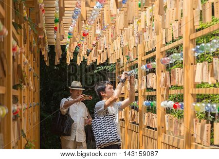 KAWAGOE JAPAN - 20 JULY 2016 - Two Asian male tourists take pictures of Glass wind chimes hanging from wood structure at Hikawa Shrine in Kawagoe town Japan on July 20 2016.