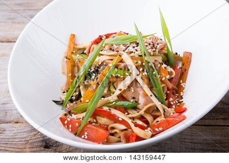 Fresh fried asian wok noodles served in white bowl