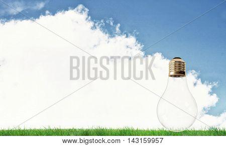 Electric light bulb against summer cloudy sky