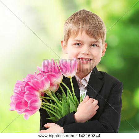 Cute boy with flowers on blurred background. Education concept.