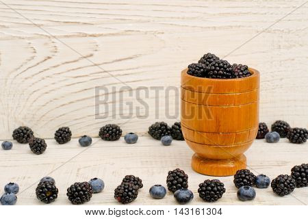 Wooden vessel with blackberries blueberries and blackberries on the edges light background
