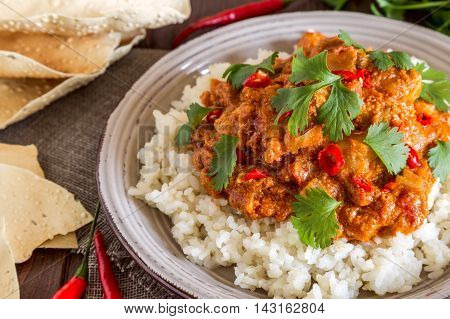 Chicken curry with rice and cilantro selective focus.