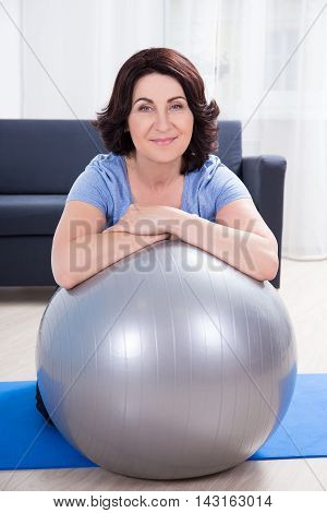 Portrait Of Slim Sporty Mature Woman Doing Exercises With Fitness Ball At Home