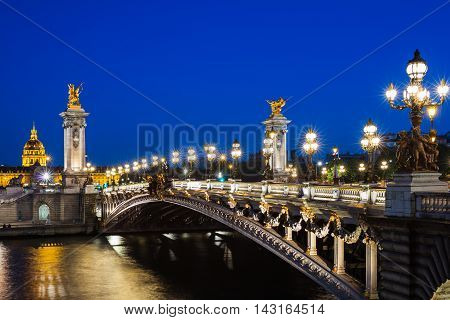 Pont Alexandre III bridge and the Hotel des Invalides in the background in the summer evening. Beautiful night illumination of bridge decorated with ornate Art Nouveau lamps and sculptures.