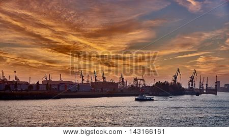 HAMBURG GERMANY - NOVEMBER 01 2015: A lonely sightseeing ship passes along the silhouette of the famous docks of the harbor of Hamburg during a scenic sundown.