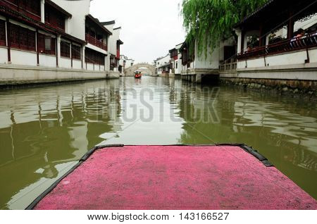 The front of a Chinese tourist boat on the water canals of Zhaojialou in Shanghai china on an overcast day.