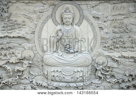 A stone mural of the sea goddess Guanyin Buddha surrounded by her disciples at the Guanyin landmark on the island of Putuoshan in zhejiang province China.