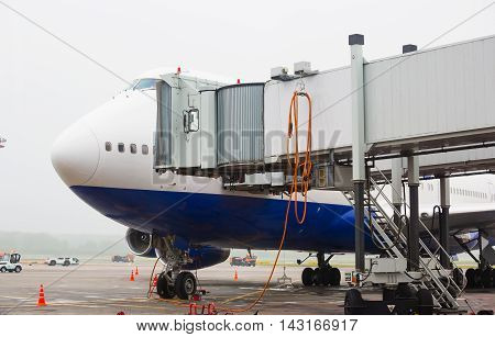 The plane at the airport loading passengers