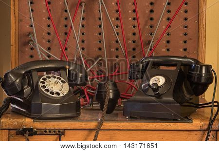 Two old black phones and a telephone exchange board.
