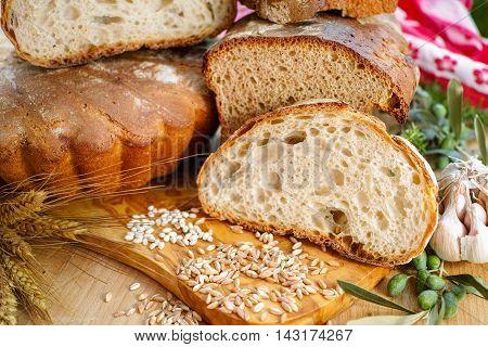 Freshly baked sourdough spelt bread and traditional italian bread on olive wood board