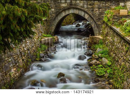 Beautiful mountain waterfall in the woods water flowing under a bridge