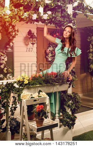 Beautiful young brunette woman in mint dress on a porch of her house
