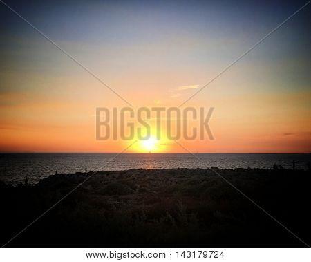 sailboat passing ahead in a beautiful sunset in menorca island