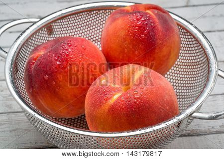 Peaches with morning dew in a stainless steel colander isolated on a white surface. Sharp focus set to front peach.