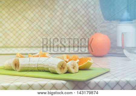 Fresh pulp banana with orange slices on kitchen table background. Blur Backside - Round fruit and blue pitcher of water. Diet, healthy concept, still life. Home made vitamin, fruits lunch. Copy space, text place.
