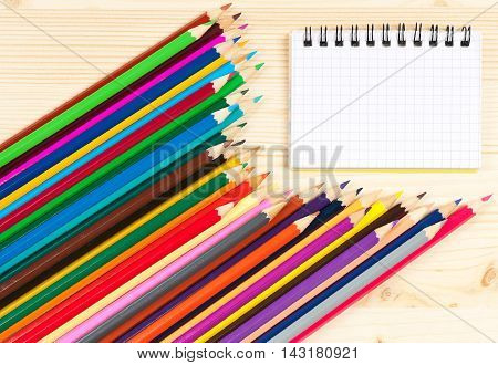 Bright colorful pencils with notebook over wooden surface