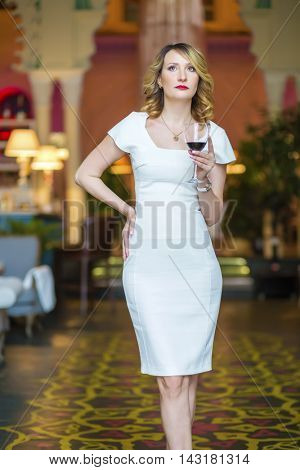 Beautiful middleaged woman in white dress stands with wine in restaurant, shallow dof