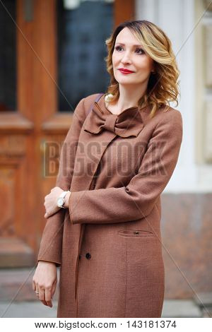 Beautiful middleaged woman in jacket stands on street and looks away, shallow dof