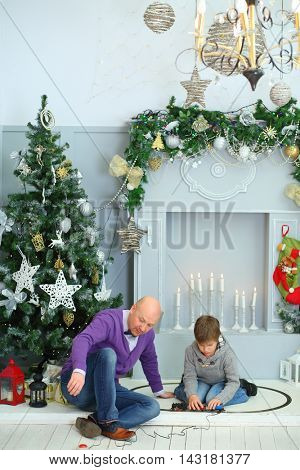 Father with his son play with model railway near christmas tree in room