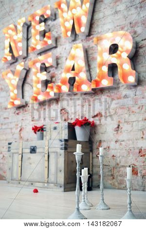 Big letters with lamps - New Year on wall and candles on floor, focus on candles