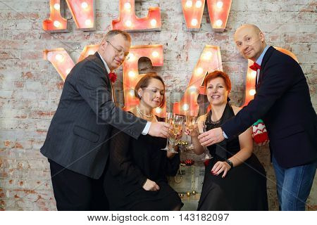 Four happy friends clink glasses with white wine near illuminated letters (New Year) in studio
