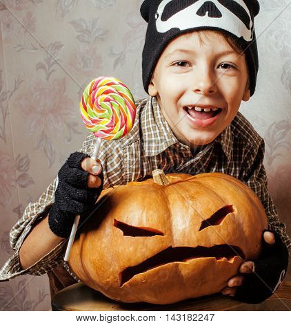 little cute boy with halloween pumpkin close up holding candy, trick or treat smiling, lifestyle people concept